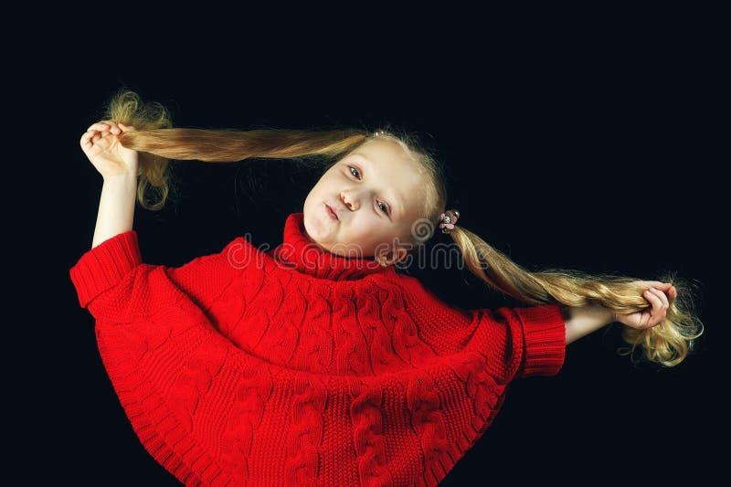 Pequeña muchacha de moda en el suéter rojo que sostiene un pelo imágenes de archivo libres de regalías