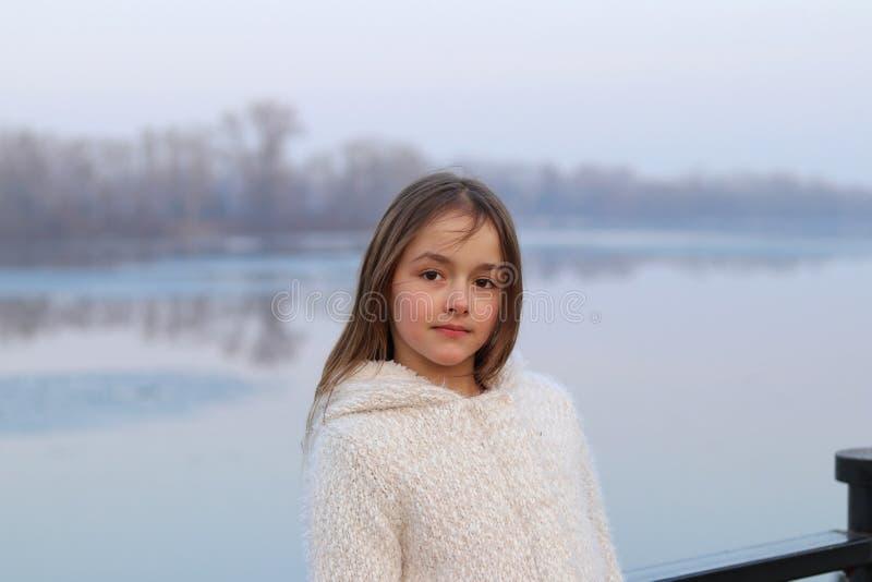 Pequeña muchacha de ojos marrones hermosa en la capa blanca que mira la cámara seriamente imagenes de archivo