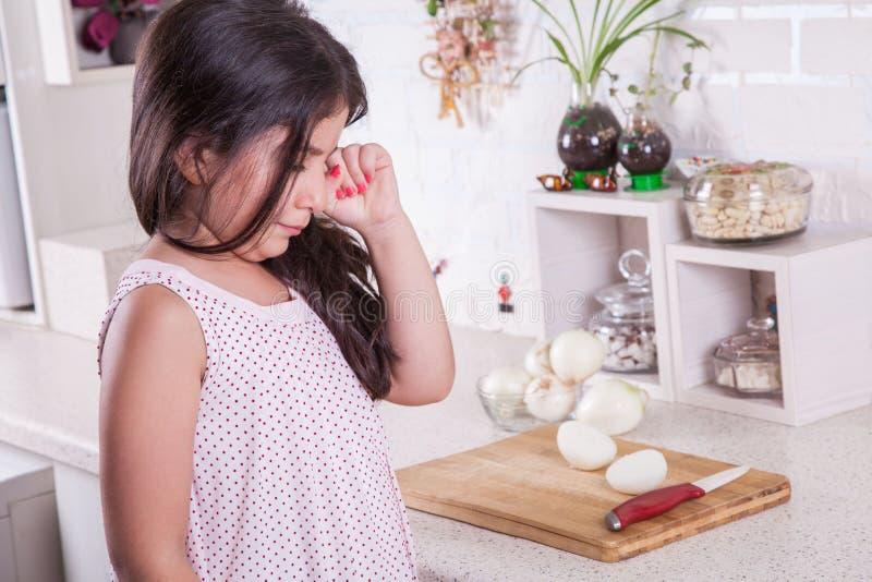 Pequeña muchacha de Oriente Medio hermosa que llora en la cocina, rasgones de la cebolla Tiro del estudio imagen de archivo