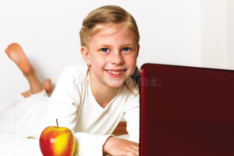 Pequeña muchacha del estudiante con PC del ordenador portátil en casa imagenes de archivo