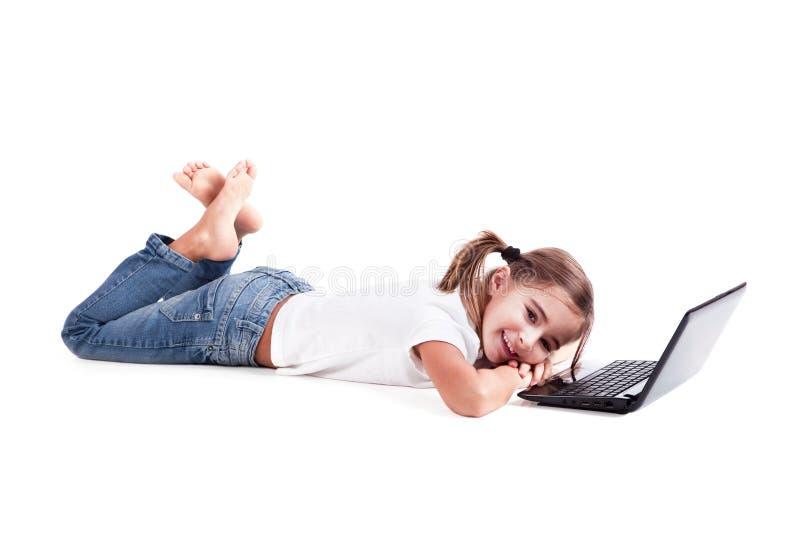 Pequeña muchacha del estudiante con una computadora portátil imagenes de archivo