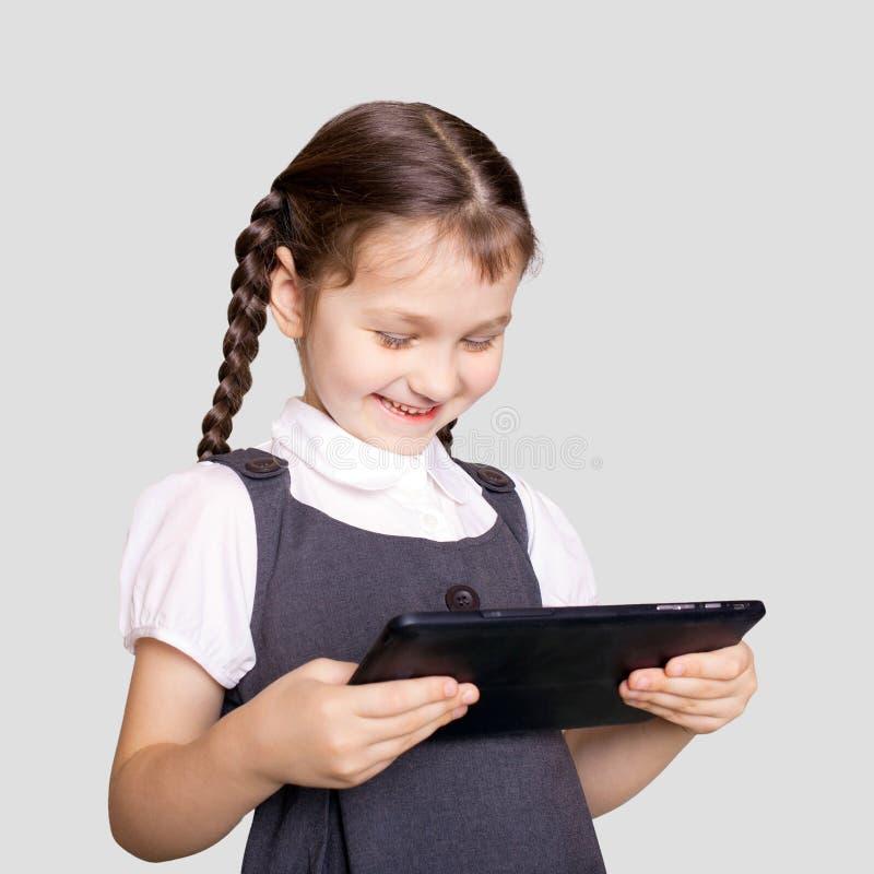 Pequeña muchacha del estudiante que usa la PC de la tableta fotografía de archivo