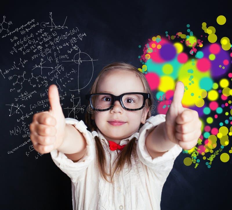 Pequeña muchacha del genio en el tablero de tiza en sala de clase con símbolo foto de archivo libre de regalías
