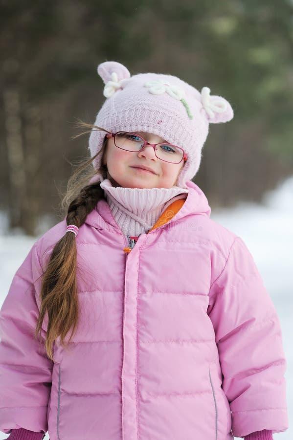 Pequeña muchacha del invierno adorable en vidrios imagen de archivo libre de regalías