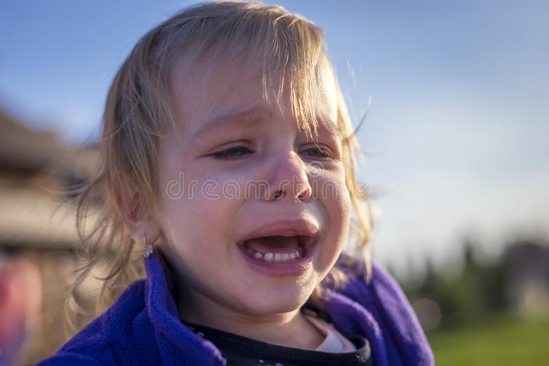 Pequeña muchacha desaliñada que llora al aire libre fotografía de archivo