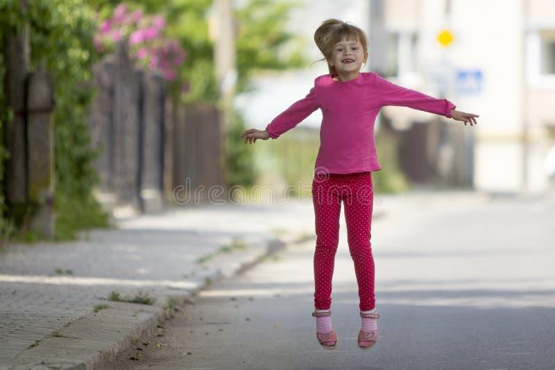 Pequeña muchacha desdentada sonriente divertida linda en ropa informal rosada con la cola de potro rubia larga que salta y que se fotografía de archivo