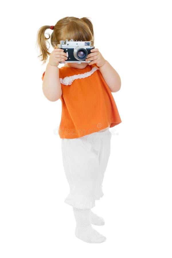 Pequeña muchacha divertida con la cámara de la foto fotos de archivo