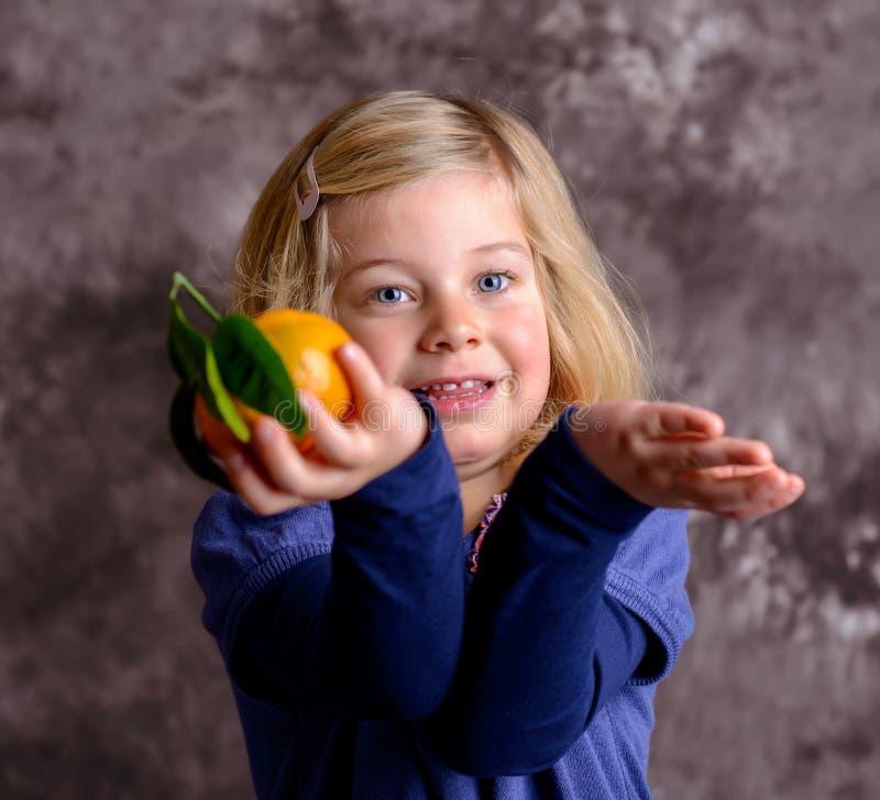 Pequeña muchacha divertida con la mandarina fotos de archivo