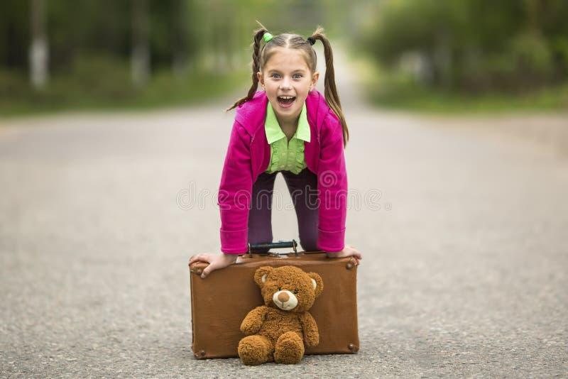 Pequeña muchacha divertida en el camino con una maleta y un oso de peluche Feliz fotografía de archivo libre de regalías