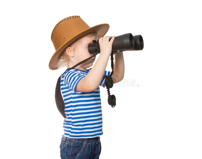 Pequeña muchacha divertida que mira a través de los prismáticos imagenes de archivo