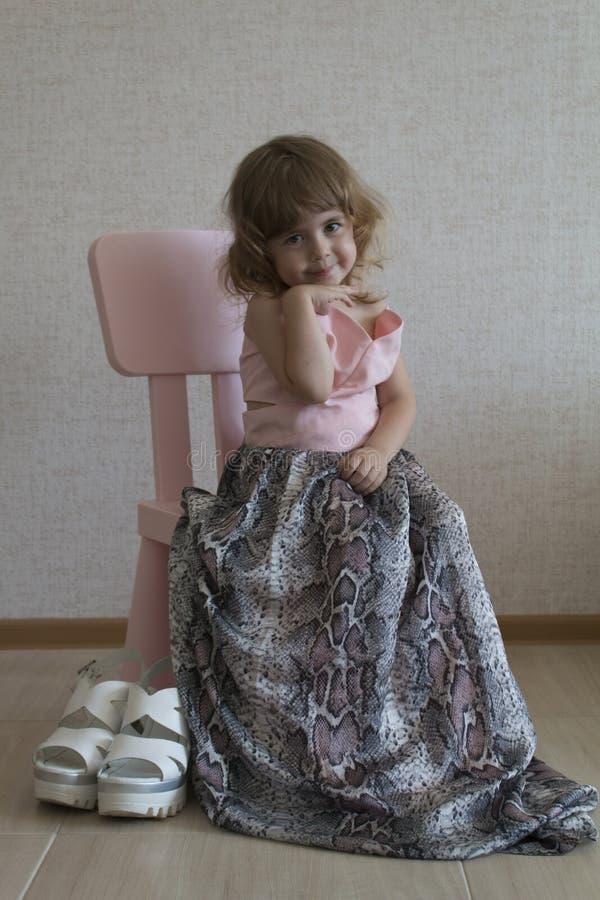 Pequeña muchacha divertida que se sienta en una silla en su vestido grande del ` s de la madre imagen de archivo libre de regalías