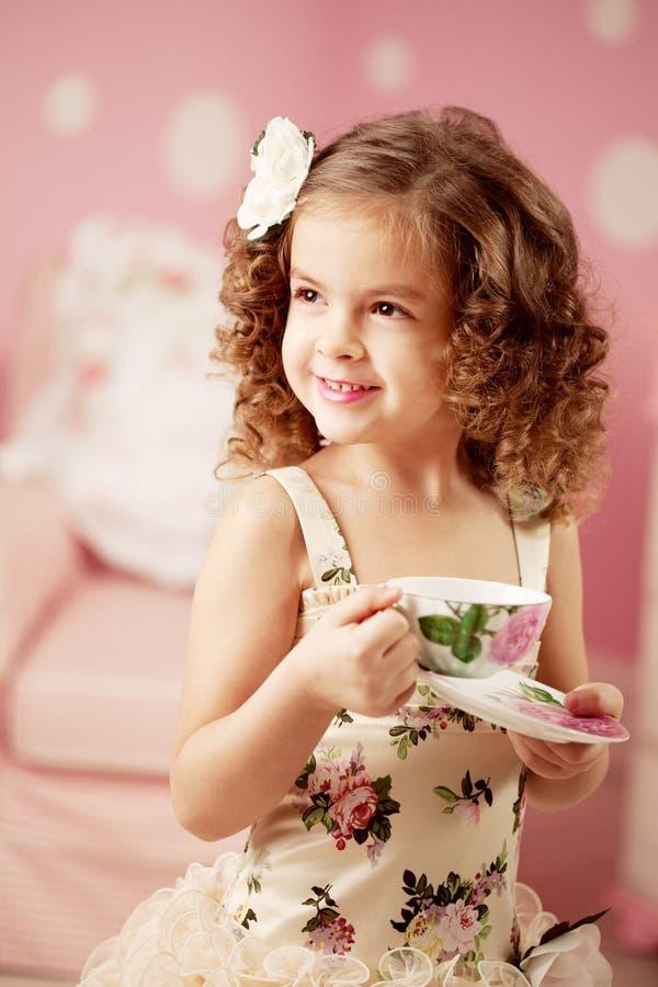 Pequeña muchacha dulce con té imagenes de archivo