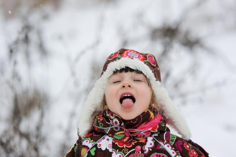 Pequeña muchacha en caída fuerte de la nieve imágenes de archivo libres de regalías