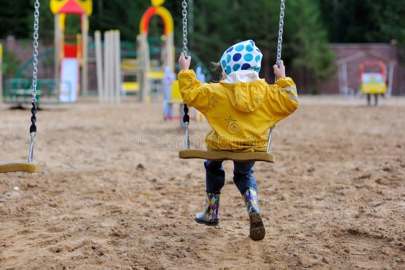 Pequeña muchacha en capa de lluvia amarilla en el oscilación foto de archivo libre de regalías