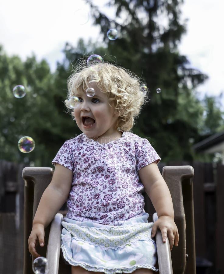 Pequeña muchacha en diapositiva con las burbujas fotos de archivo