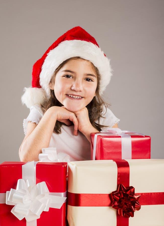 Pequeña muchacha en el sombrero de santa con el regalo de la Navidad imágenes de archivo libres de regalías