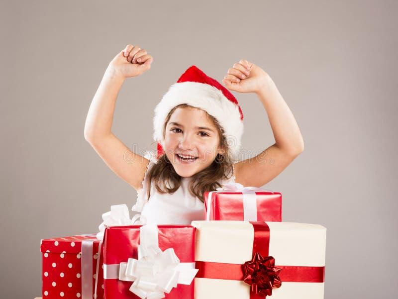 Pequeña muchacha en el sombrero de santa con el regalo de la Navidad imagenes de archivo
