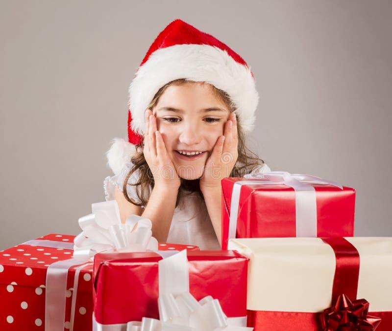 Pequeña muchacha en el sombrero de santa con el regalo de la Navidad foto de archivo libre de regalías
