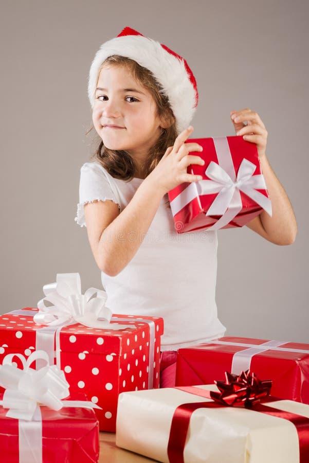 Pequeña muchacha en el sombrero de santa con el regalo de la Navidad fotos de archivo libres de regalías