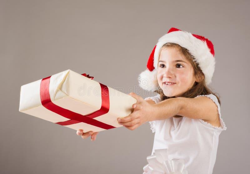 Pequeña muchacha en el sombrero de santa con el regalo de la Navidad fotos de archivo