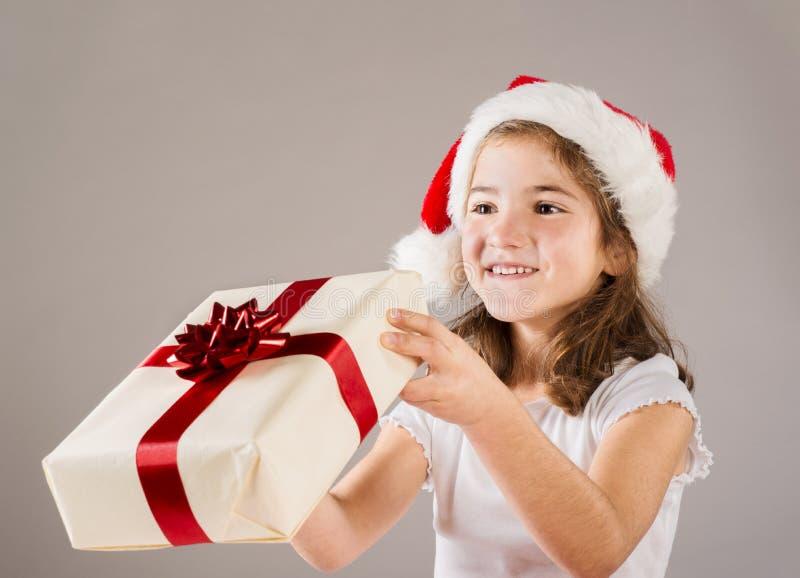 Pequeña muchacha en el sombrero de santa con el regalo de la Navidad imagen de archivo libre de regalías