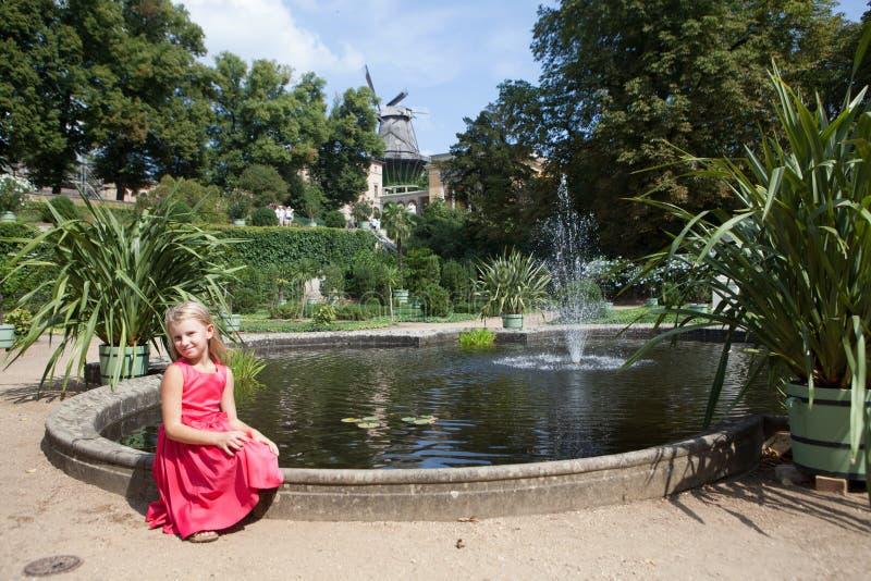 Pequeña muchacha en parque con la fuente foto de archivo libre de regalías