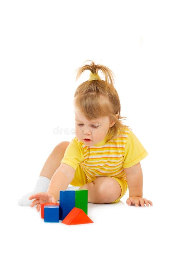 Pequeña muchacha en pirámide amarilla del juguete de la estructura fotografía de archivo