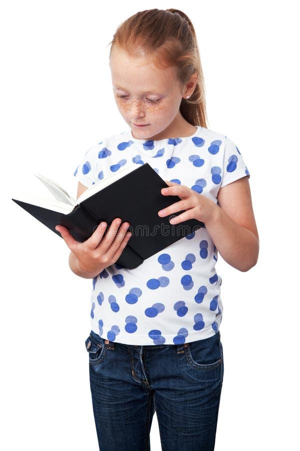 Pequeña muchacha estudiosa que lee un libro fotos de archivo libres de regalías