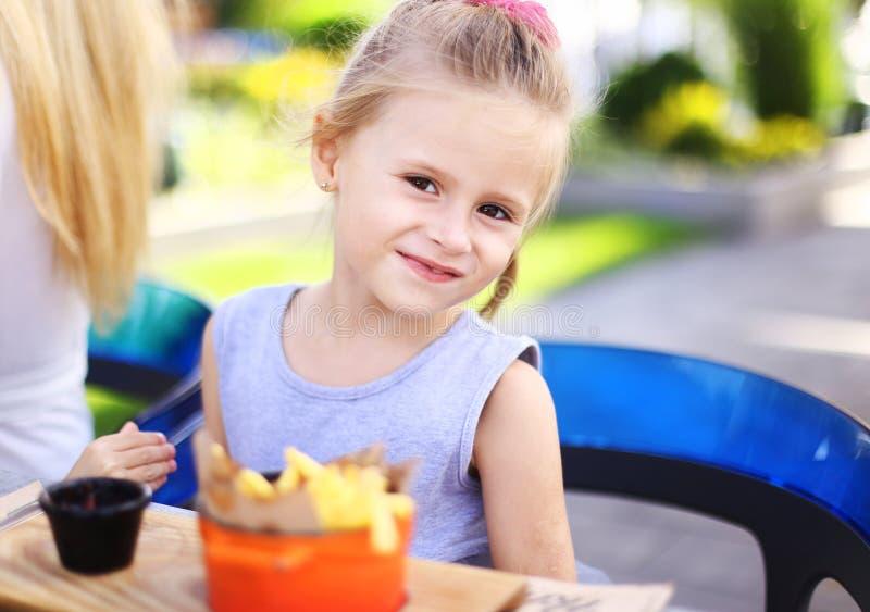 Pequeña muchacha europea que come las fritadas del rench con la salsa en el café de la calle afuera foto de archivo libre de regalías