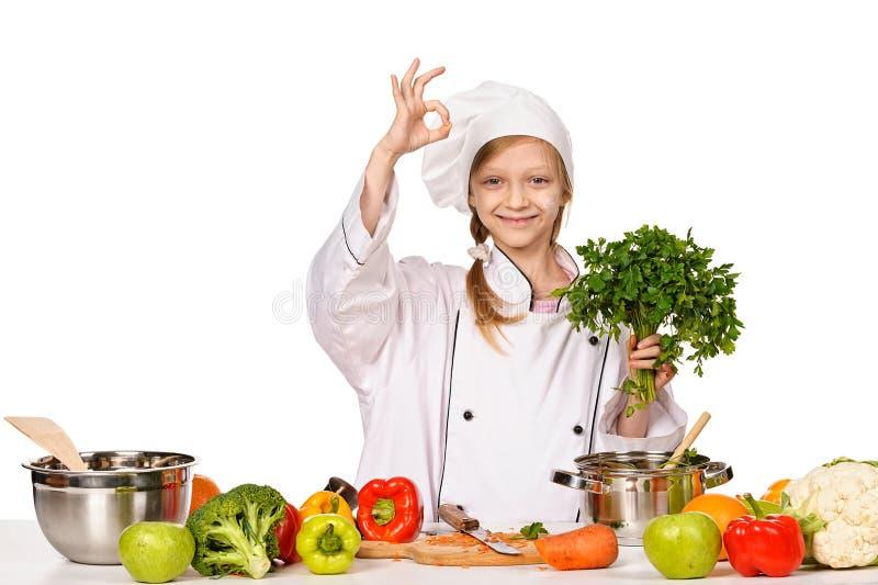 Pequeña muchacha feliz del cocinero con el perejil que muestra OK foto de archivo