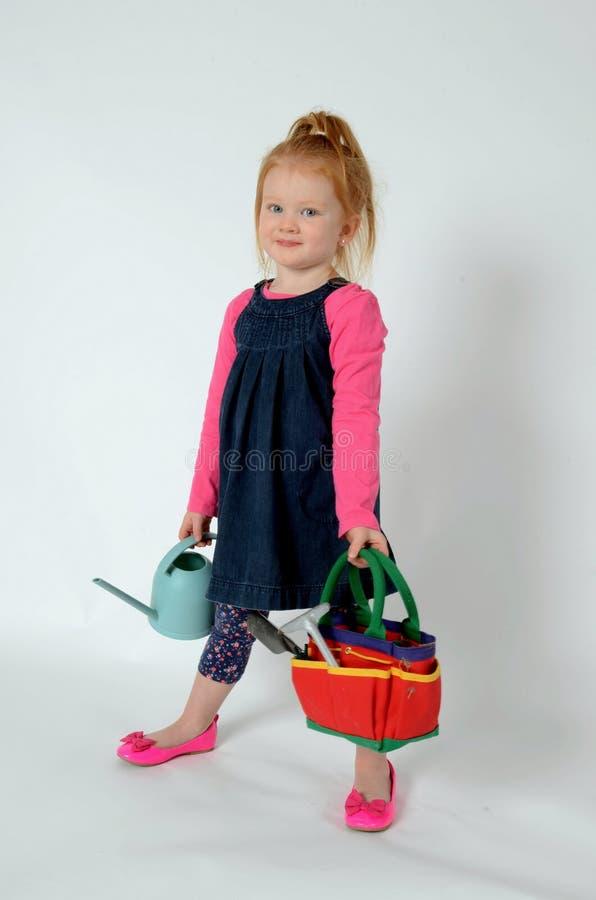 Pequeña muchacha feliz del redhead con las fuentes del jardín foto de archivo