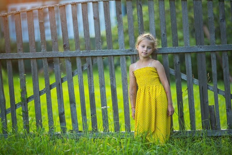Pequeña muchacha feliz en vestido amarillo cerca de la cerca de madera en el pueblo imagen de archivo libre de regalías