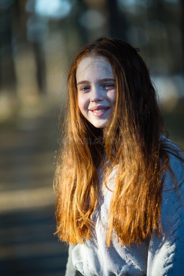 Pequeña muchacha feliz pelirroja que presenta para un retrato en el parque fotos de archivo