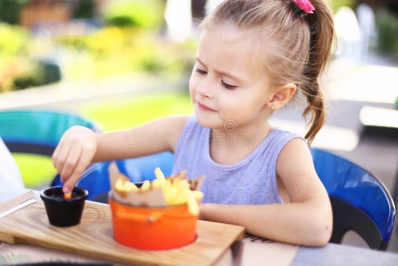 Pequeña muchacha feliz que come las fritadas del rench con la salsa en el café de la calle afuera fotos de archivo libres de regalías