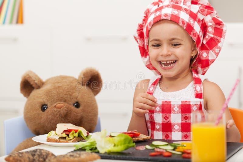 Pequeña muchacha feliz que come un bocado con su oso de peluche imagenes de archivo