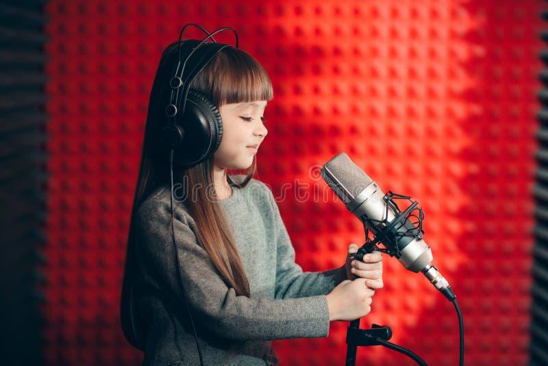 Pequeña muchacha hermosa agradable que mira el micrófono mientras que canta la canción imagen de archivo libre de regalías