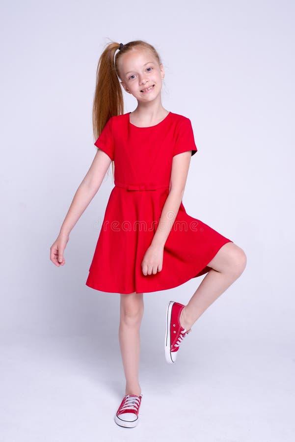 Pequeña muchacha hermosa del pelirrojo en vestido rojo y las zapatillas de deporte que presentan como modelo en el fondo blanco imagen de archivo libre de regalías
