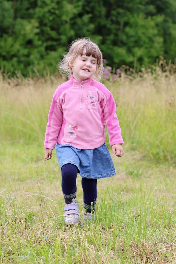Pequeña muchacha hermosa en ir de la falda y Hamming en el prado verde fotografía de archivo libre de regalías