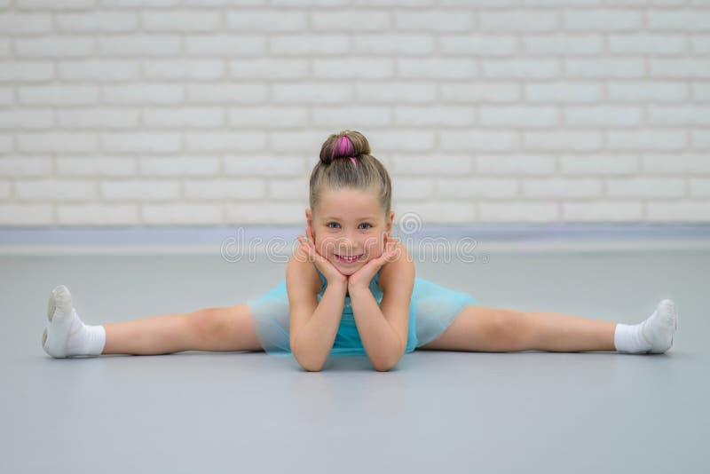 Pequeña muchacha hermosa linda que hace fracturas en la clase del ballet Bailarina feliz joven en estirar azul del vestido, sonri imagen de archivo