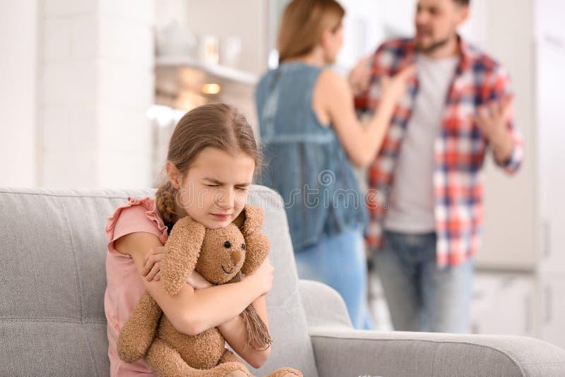 Pequeña muchacha infeliz que se sienta en el sofá mientras que discusión de los padres imagen de archivo libre de regalías