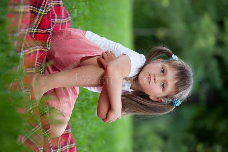 Pequeña muchacha irritada que se sienta en la tela escocesa en hierba fotos de archivo libres de regalías