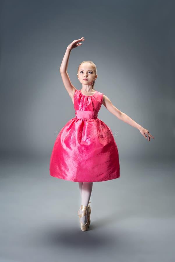 Pequeña muchacha joven de la bailarina en el vestido rosado que hace fractura gimnástica fotografía de archivo