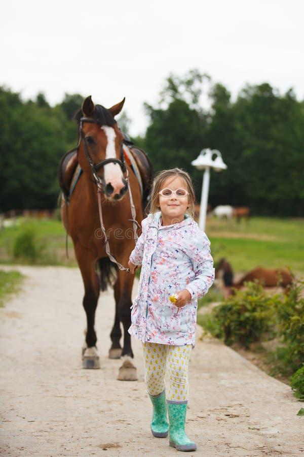 Pequeña muchacha linda con el caballo imagenes de archivo