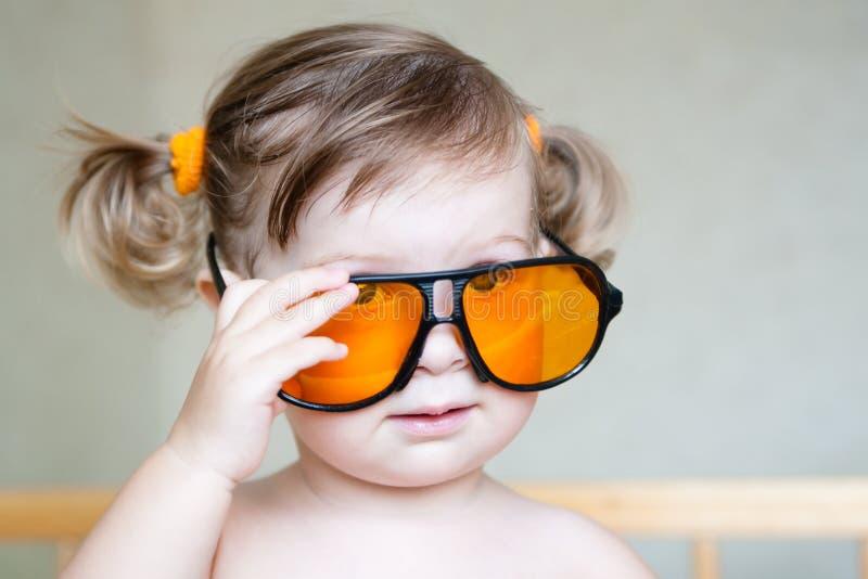 Pequeña muchacha linda con las gafas de sol anaranjadas imagen de archivo libre de regalías
