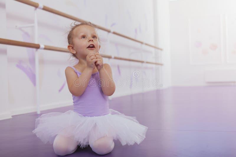 Pequeña muchacha linda de la bailarina que ejercita en la escuela de danza foto de archivo