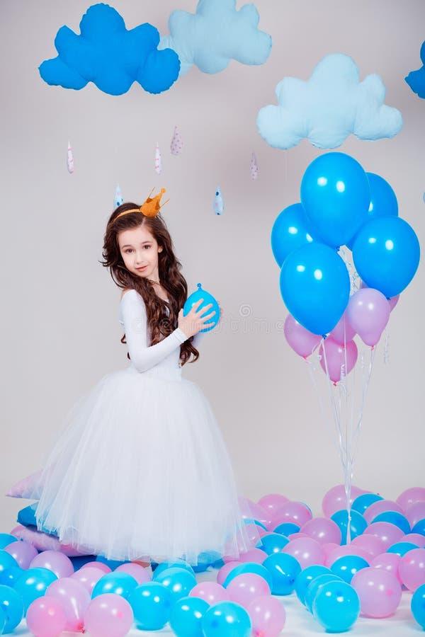Pequeña muchacha linda de la princesa que se coloca entre los globos en sitio sobre el fondo blanco mirada de la cámara Niñez imagenes de archivo