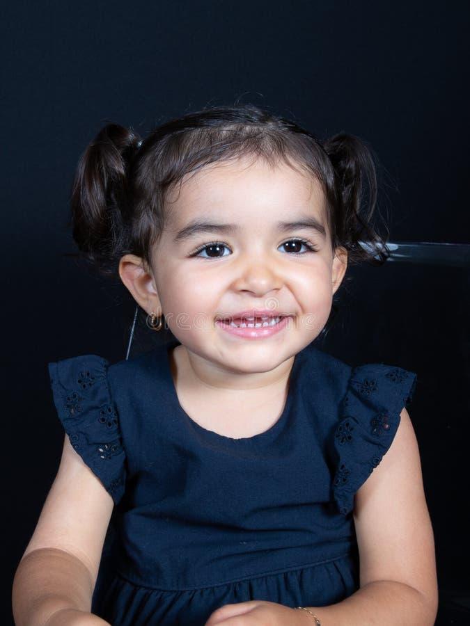 Pequeña muchacha linda de risa dulce en el retrato negro del fondo fotografía de archivo