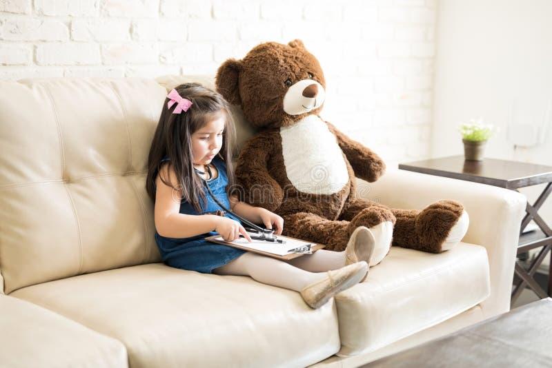 Pequeña muchacha linda del doctor que juega con el oso de peluche imagen de archivo