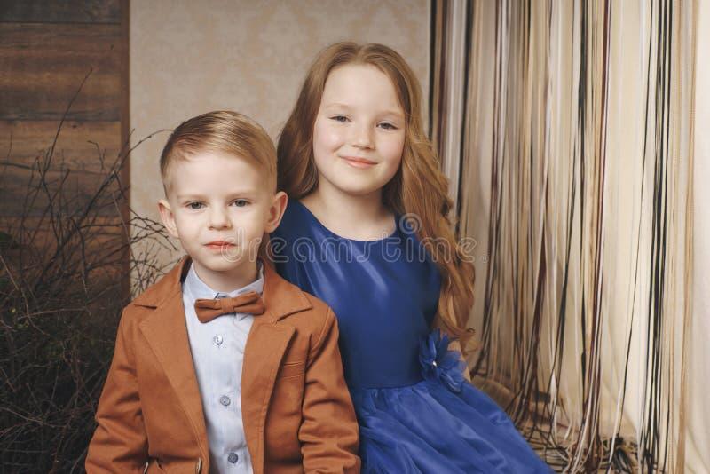 Pequeña muchacha linda del muchacho que abraza jugar en el fondo blanco, cierre feliz de la familia encima del hermano y la sonri imagen de archivo