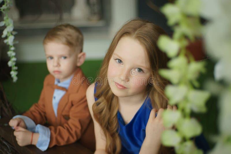 Pequeña muchacha linda del muchacho que abraza jugar en el fondo blanco, cierre feliz de la familia encima del hermano y la sonri foto de archivo libre de regalías